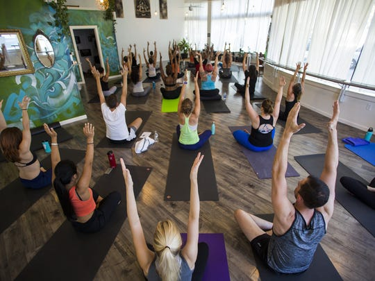 """Before rapper Future's """"Mask Off"""" comes on over the speakers, Abiola Akanni's Trap Vinyasa class warms up to calmer tunes at Bohemian Studios.  (Kjell Redal/The Seattle Times/TNS)"""