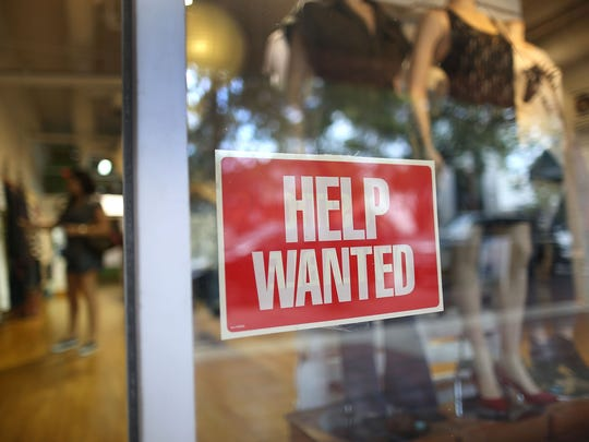File photo taken in 2015 shows a help wanted sign in the Unika store in Miami.