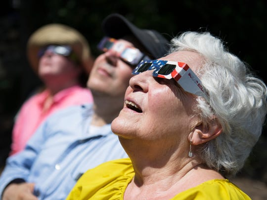 "Josefa Trevino of Raleigh looks up at the solar eclips in downtown Greenville on Monday, August 21, 2017. ""I'm 83 and this is my first time seeing one,"" she said."