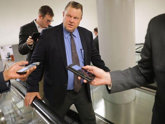 Sen. Jon Tester talks to reporters en route to a Senate