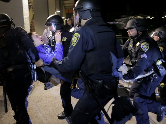 A protester is carried into a building by police officers