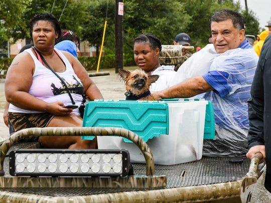 Volunteers and first responders work together to rescue residents from rising flood waters from Hurricane Harvey in Houston, Aug. 29, 2017.