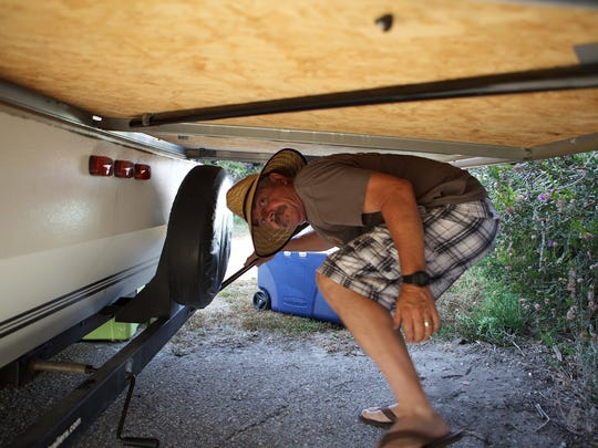 Tim Lysaght sets up his camper during opening day of McGrath State Beach on Friday. Lysaght arrived at 5 a.m. to get his campsite near Ventura Harbor.