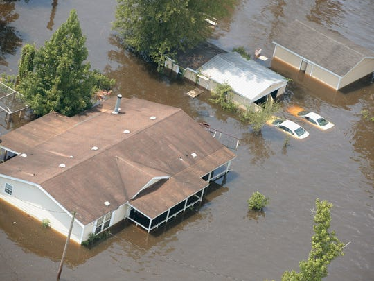 A home is surrounded by floodwater after torrential