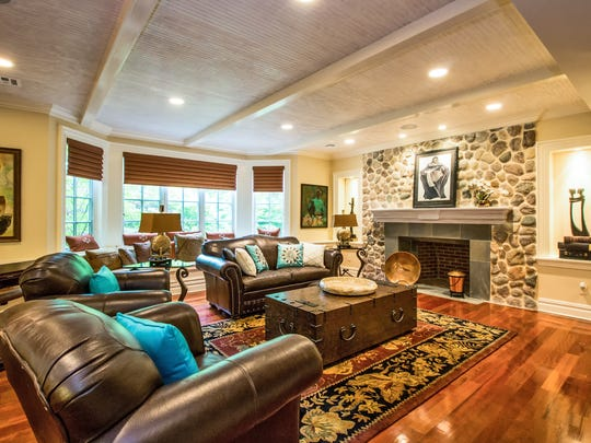 This family room features a beamed ceiling, bay window, hardwood floors and a floor-to-ceiling stone fireplace.