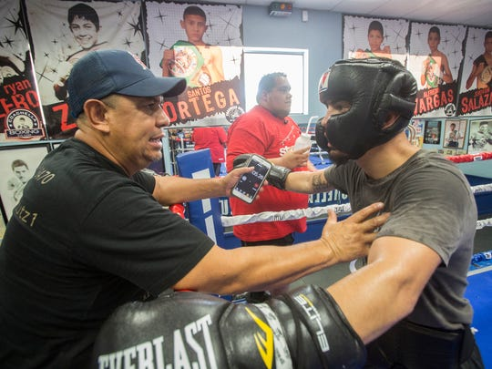 At left, Marcos Caballero, the father and trainer of Randy Caballero talks to the younger Caballero about strategy during a training session in preparation for his bout against Diego De La Hoya on September 16, 2017.