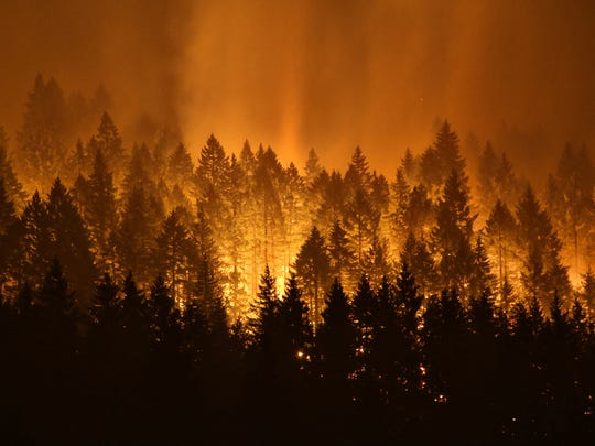 A wildfire continues to burn on the Oregon side of the Columbia River Gorge near Cascade Locks, Ore., and the Bridge of the Gods, late Tuesday, Sept. 5, 2017.