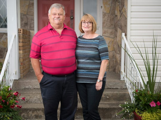 Dave and Queen Blundon in front of their home in Gander.