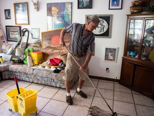 Charlie Kirk mops his floor as he begins cleaning up
