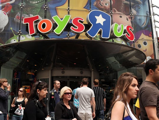 "People walk by Toys ""R"" Us in Times Square in New York City. (2010 photo by Spencer Platt/Getty Images)"