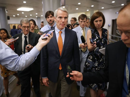 Sen. Rob Portman (R-OH) (C) is pursued by reporters