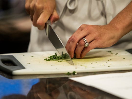 Maggie Norris chops parsley during a private class at Whisked Away, a cooking school for home chefs, on Sept. 12, 2017, in Phoenix. Norris has been teaching the classes from her home since 2009.