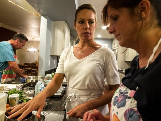 Maggie Norris, left, assists Berkeley Lopez during a private class at Whisked Away, a cooking school for  home chefs, on Sept. 12, 2017, in Phoenix. Norris has been teaching the classes from her home since 2009.