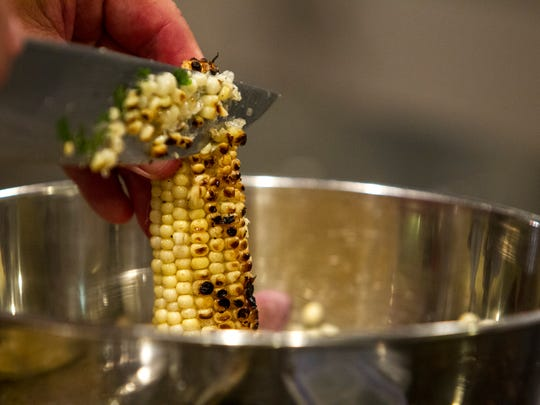 Michael Lopez cuts corn off the cob during a private class at Whisked Away, a cooking school for home chefs, on Sept. 12, 2017, in Phoenix. Maggie Norris has been teaching the classes from her home since 2009.