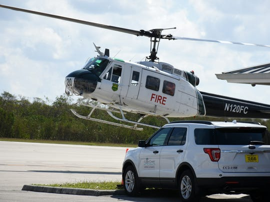 A Forest Service helicopter lands at the airport. The Civil Air Patrol's hangar at the Marco Island Executive Airport was smashed by an extremely local event during Hurricane Irma.