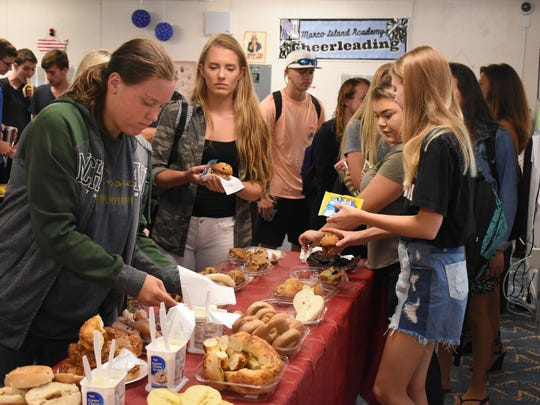 "Students enjoy the breakfast Principal Melissa Scott called ""Cat 4 continental"" after the flag-raising ceremony. Marco Island Academy, the island's charter high school, marked its first day of classes after Hurricane Irma on Monday, Sept. 25, 2017, with a ceremony featuring a flag that had flown in war zones."