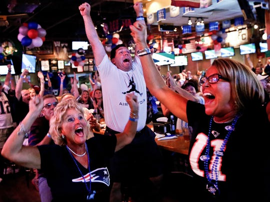 Boston natives Karen Dugan, from left, John Dugan, and Lisa Doyle celebrate as the New England Patriots scored their second touchdown against the Seattle Seahawks before halftime in the Superbowl while they watched with their fellow Patriot fans at Foxboro Sports Tavern on Sunday, February 1, 2015. (Scott McIntyre/Staff)