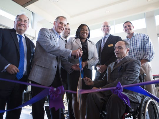 Mayor Lovely Warren cuts the ribbon with Strathallan owners Dave Christa and Bob Morgan during the grand opening of the rooftop space at the Strathallan Hotel on Wednesday, June 3, 2015.