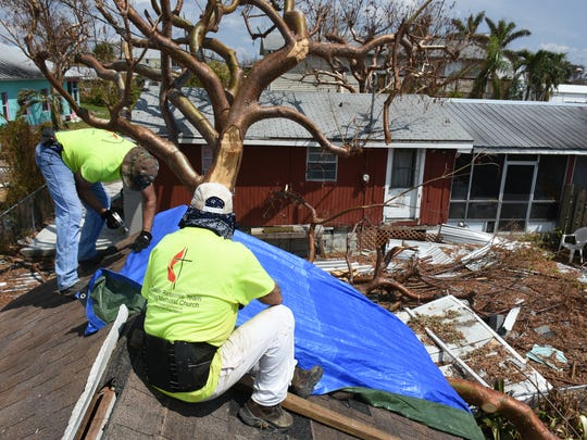 Disaster relief volunteers coordinated by the Wesley United Methodist Church cover a roof on Goodland with a tarp. The group drove down from Tennessee to help residents after Hurricane Irma.