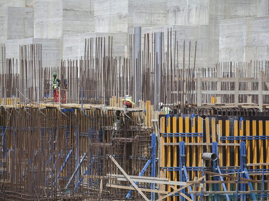 Workers stand on scaffolding during the construction