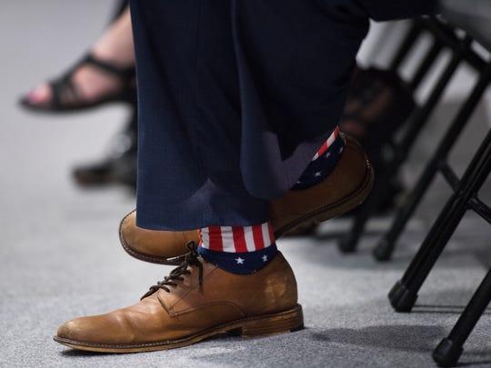 An audience member wears American flag socks as Reverend