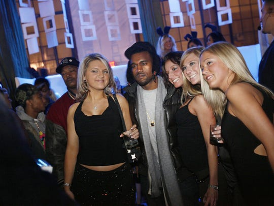 Hip hop artist Kanye West  poses for a photo with fans during the Playboy Super Bowl Party at the Coleman A. Young Municipal Airport, Saturday, Feb. 4, 2006.