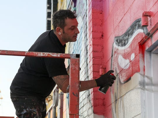 "Windsor-based artist Daniel Bombardier, better known as the street artist ""Denial,"" paints his mural during the Eastern Market After Dark event Thursday, Sept. 28, 2017 in downtown Detroit. The After Dark event coincides with the final day of the annual Murals in the Market festival that saw nearly 30 new large-scale paintings decorate the district."