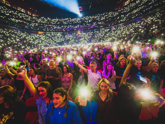 Fans light up their cellphone flash lights at a sold-out Ed Sheeran concert on September 27, 2017.