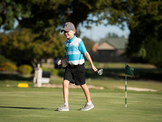 Jackson Merriss, 8, smiles after practicing his putting