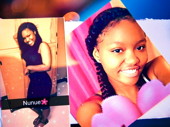 Family members hold a photo of 16-year-old Deberianah