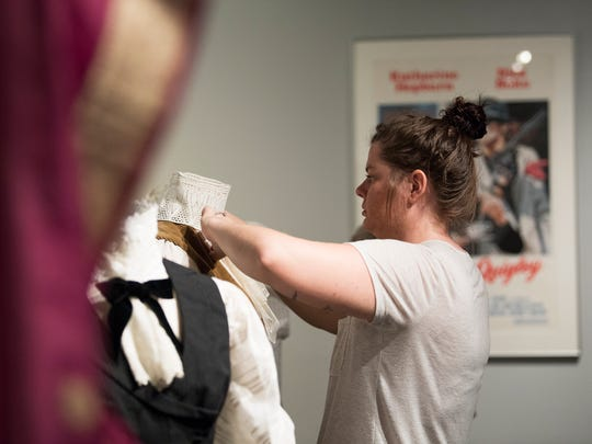 """Paula Valls sets up a display of costumes worn by Katharine Hepburn in anticipation of the upcoming """"Katharine Hepburn: Dressed for Stage & Screen"""" exhibit at the Upcountry History Museum on Wednesday, Oct. 11, 2017."""