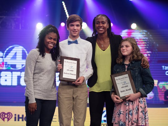Bria Felicien with the Greenville News and Tamika Catchings present the Greenville News award to Sevier Middle School eighth graders Bailey Betsill and Jackson Duncan during Coaches 4 Character at Redemption Church on Tueday, October 17, 2017.