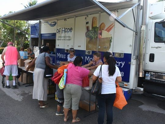 Recipients fill their containers at Lely Presbyterian