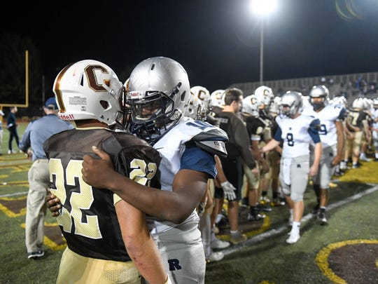 Reitz's Da'Ziaun Sargent (10) gives Central's Reeder Pennell (22) a hug as the teams shake hands following Central's 34-6 win in the Class 4A football sectional opener at Central High Friday, October 20, 2017.