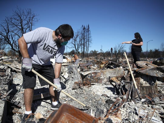 Ben Hernandez Jr., left,  sifts through the remains of his Coffey Park home that was destroyed by the Tubbs Fire.