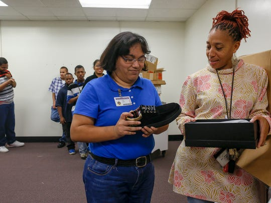 Student, April Smith, left, holds her brand new shoe next to her teacher Tracie Diggins, right, on Tuesday, Oct. 24, 2017 at the Drew Transition Center in Detroit. DeAngelo Rocklin Jackson-Portwood, known as Rocklin Negash, is the creator and CEO of Negash, and is donating 500 pairs of shoes or nearly $20,000 worth of footware to the students at Drew Transition Center.