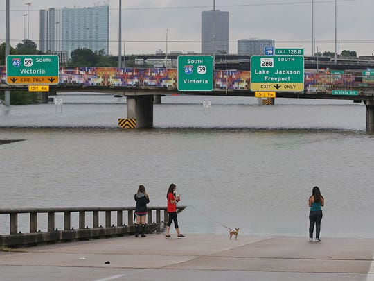 TOPSHOT - People view the flooded highways in Houston