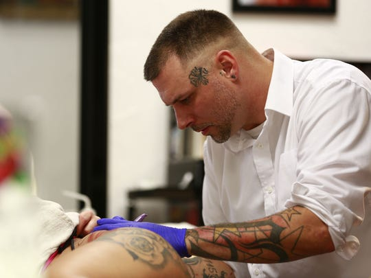 Tattoo artist Tommy Kirschbaum uses a sharpie to sketch a drawing on a customer's hip on Monday, October 2, 2017, at Mid-West Tattooers in Marshfield, Wisconsin.