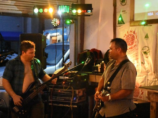 """Chris Johnson, left, and """"Tastes Like Chicken"""" entertain at the Swamp Brew event."""