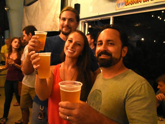 Ian Easterling, from left, Samantha Arner and Ian Bartoszek contribute to the cause at the Swamp Brew event.