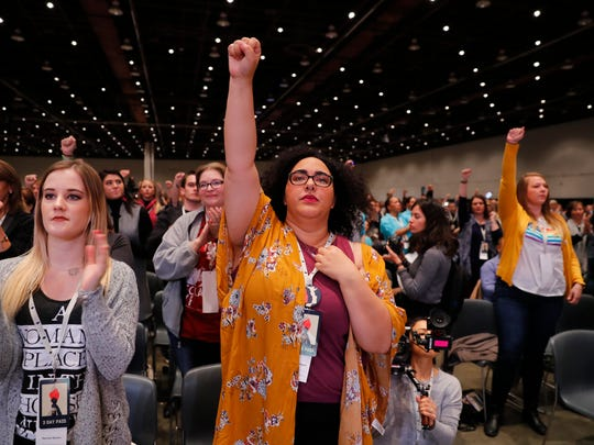 Women stand while listening to actress Rose McGowan at the inaugural Women's Convention in Detroit, Friday, Oct. 27, 2017. McGowan recently went public with her allegation that film company co-founder Harvey Weinstein raped her.