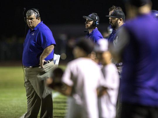 Queen Creek head coach Travis Schureman watches from