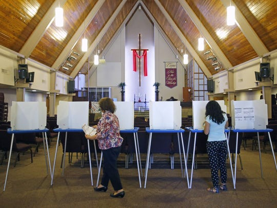 Poll workers stock voting booths May 16, 2016, at the