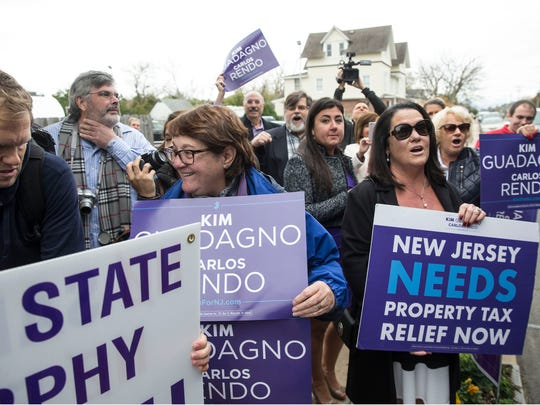 Voters gather in Monmouth Beach with signs Tuesday.
