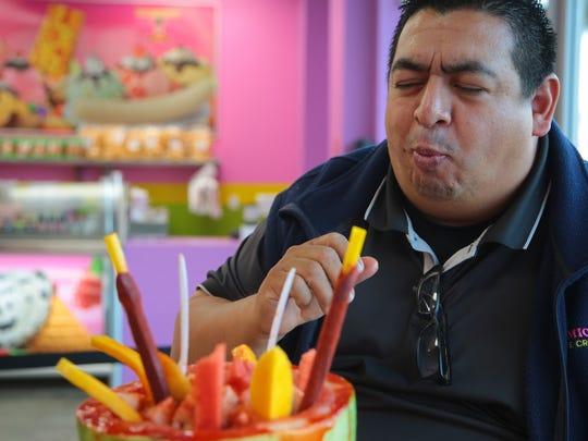 La Michoacana owner David Bermudez bites into a Sandia