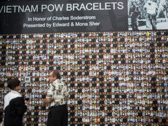 This wall inside the new Palm Springs Air Museum's Maj. Gen. Ken Miles hangar displays the names and photographs of Americans held prisoner or missing in action in the Vietnam War. Next to the wall are two digital touch screens filled with biographical information about each of the names on the wall.
