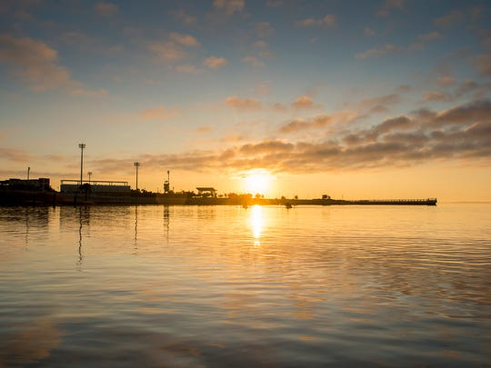 The sun rises over Maritime Park as seen from Bruce Beach in Pensacola on Tuesday, November 7, 2017.  A fish hatchery is proposed to be built on the Bruce Beach property.