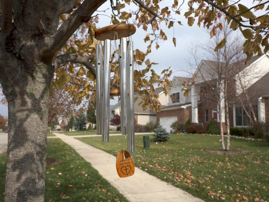 A wind chime hangs from a tree in the front of the
