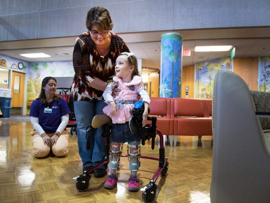 Brayden Dame, 6, gets help from her grandma, Dawn Dame,