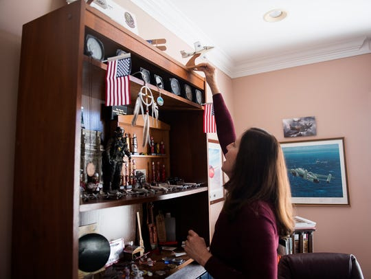 Jane Dyer places a model airplane on a display shelf